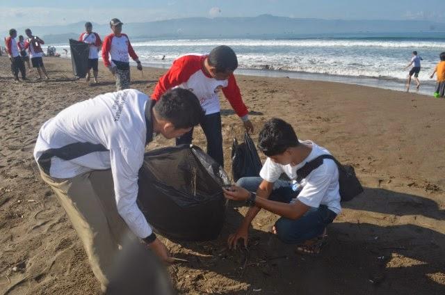 Nelayan sedang Memungut Sampah di Pantai
