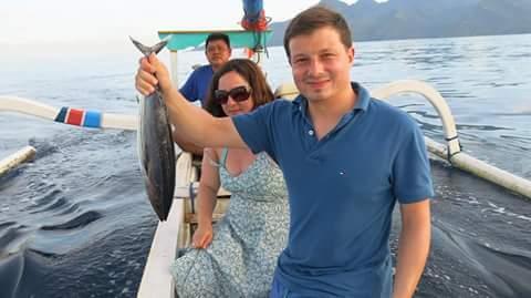 aktivitas wisatawan mancing menggunakan perahu nelayan setempat